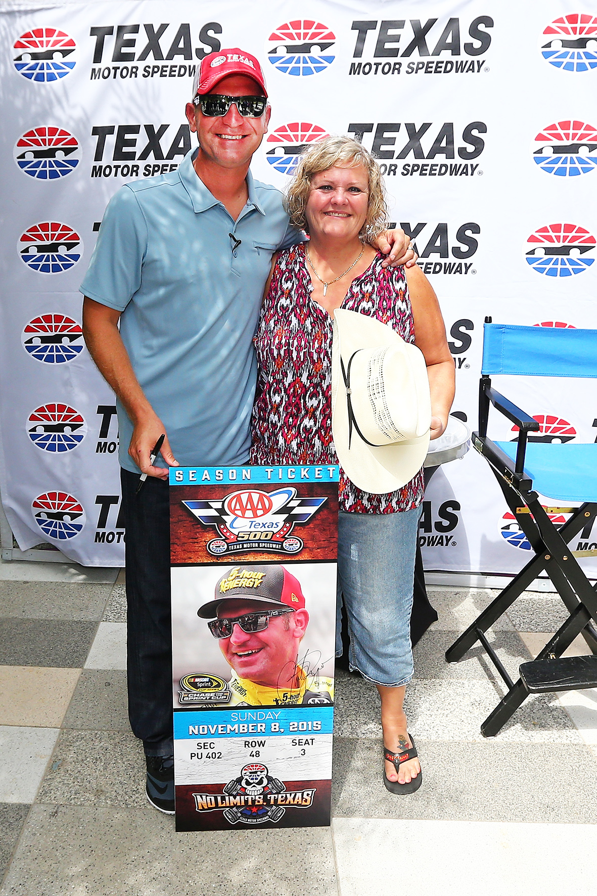"DALLAS, Texas - SEPTEMBER 15: NASCAR Sprint Cup Series driver Clint Bowyer (L) poses with Texas Motor Speedway season ticketholder Judy McMains after a surprise visit as part of NASCAR's Chase Across North America Day on September 15, 2015 at Klyde Warren Park in Dallas, Texas. Bowyer posed as a pestering videographer for a fictitious ""Texas Motor Speedway Fan Appreciation Day"" before revealing his identity and surprising the season ticketholder. (Photo by Sarah Crabill/Getty Images for Texas Motor Speedway) *** Local Caption *** Clint Bowyer; Judy McMains"