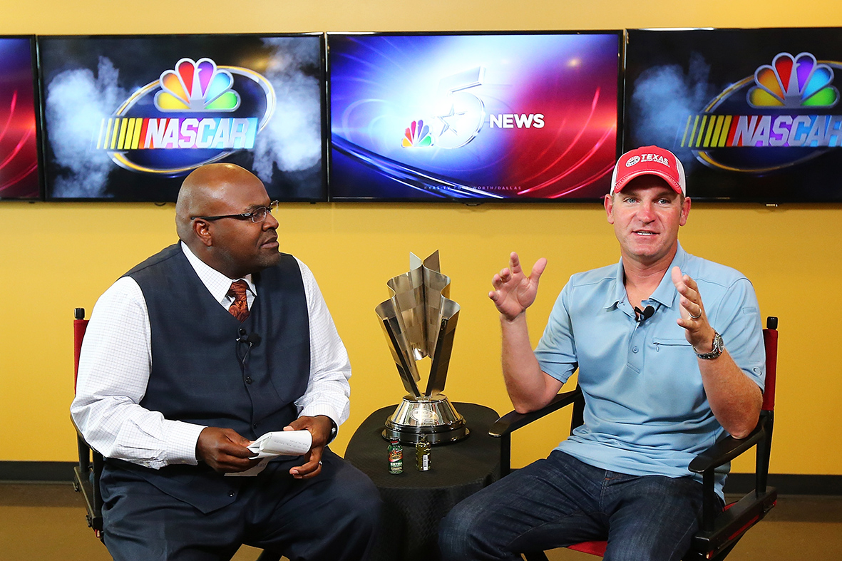 FORT WORTH, Texas - SEPTEMBER 15: NASCAR Sprint Cup Series driver Clint Bowyer (R) is interviewed by KXAS NBC-5 Sports Director Newy Scruggs for the staff members during a visit to the station's newsroom as part of NASCAR's Chase Across North America Day on September 15, 2015 in Fort Worth, Texas. (Photo by Sarah Crabill/Getty Images for Texas Motor Speedway) *** Local Caption *** Clint Bowyer