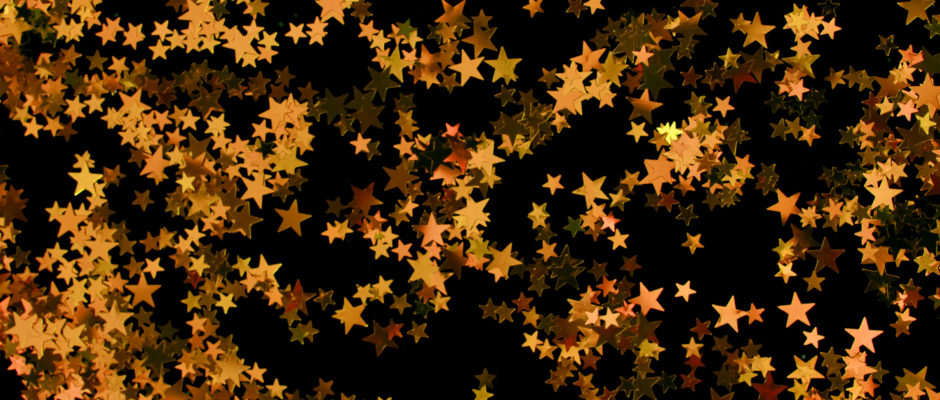 a background image of a scattering of orange glitter stars on black