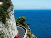 Rental 1973 Alpha Romeo driving on hairpin bends of Amalfi coast.